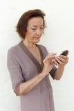 Texting superior irritado da mulher Imagem de Stock