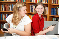 Texting Teenagers. Teen girls having a conversation via text in the library Stock Image