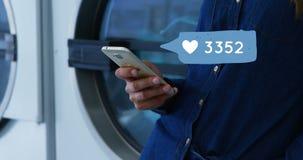 Texting terwijl terwijl het doen van wasserij 4k stock videobeelden