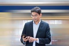 Texting terwijl het wachten van trein Royalty-vrije Stock Foto