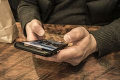 Texting with thumbs at a coffe shop wood table with brown bag royalty free stock images