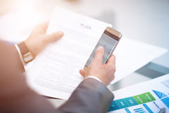 Texting to colleague. Confident young man in suit holding smart phone and looking at it while sitting at his working. Place in office Stock Photography