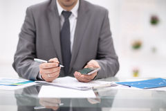 Texting to colleague. Confident young man in suit holding smart phone and looking at it while sitting at his working. Place in office Stock Photos