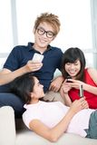 Texting together. Group of cheerful teen friends texting together Stock Photo