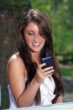 Texting trigueno adolescente hermoso al aire libre Imagen de archivo