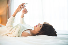 Texting woman. Beautiful young woman lying in bed and texting Royalty Free Stock Photos