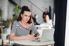 Texting woman sitting at the table and holding the mobile phone, thinking. Adult female sitting with a laptop and Royalty Free Stock Photo