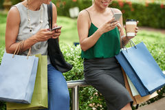 Texting women. Cropped image of women with shopping bags texting Royalty Free Stock Image