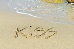 Kuss geschrieben auf sandigen Strand stockbild