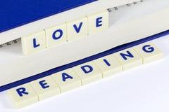 TextläsningFÖRÄLSKELSE som LÄSER mellan sidor av boken Royaltyfri Foto