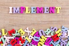 Texto 'implementar 'de letras de madeira coloridas fotos de stock royalty free