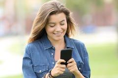 Texto adolescente de la lectura en un teléfono elegante Fotografía de archivo libre de regalías