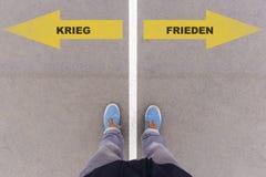 Texto alemán de Krieg/de Frieden para la guerra o paz en la tierra del asfalto, Fotografía de archivo libre de regalías