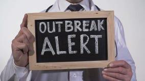 Texto alerta del brote escrito en la pizarra en manos del doctor, advertencia epidémica metrajes
