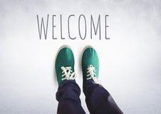 Texto bem-vindo e sapatas verdes nos pés com fundo cinzento Fotos de Stock
