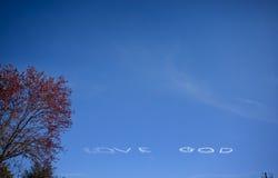Texto blanco de DIOS del AMOR creado en el cielo azul Foto de archivo libre de regalías