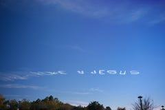 Texto blanco del AMOR U JESÚS creado en el cielo azul Imágenes de archivo libres de regalías