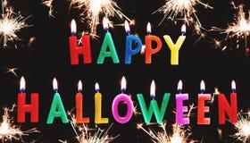 Texto colorido de la vela del feliz Halloween con los fuegos artificiales de la bengala, en fondo negro Fotos de archivo