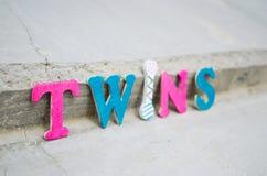 Texto colorido dos gêmeos no pavimento Fotografia de Stock Royalty Free