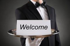Texto da boa vinda de Holding Plate With do garçom no papel imagens de stock royalty free
