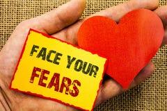 Texto da escrita que mostra a cara seus medos Conceito do negócio para a bravura corajoso da confiança de Fourage do medo do desa fotografia de stock royalty free
