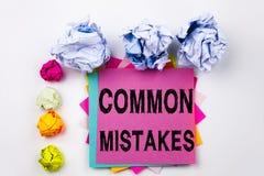 Texto da escrita que mostra os erros comuns escritos na nota pegajosa no escritório com as bolas do papel do parafuso Conceito do Fotos de Stock Royalty Free
