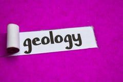 Texto da geologia, conceito da inspiração, da motivação e do negócio no papel rasgado roxo foto de stock royalty free