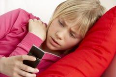 Texto da leitura da rapariga e vista preocupado Imagem de Stock