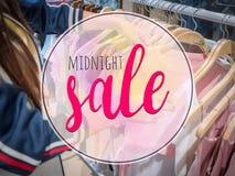 Texto da meia-noite da venda com a loja de roupa do borrão no shopping ilustração stock
