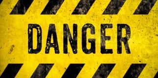 Texto da palavra do sinal de aviso do PERIGO como o estêncil com as listras amarelas e pretas pintadas sobre o fundo do muro de c fotografia de stock royalty free