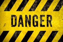 Texto da palavra do sinal de aviso do PERIGO como o estêncil com as listras amarelas e pretas pintadas sobre o fundo da textura d imagens de stock royalty free
