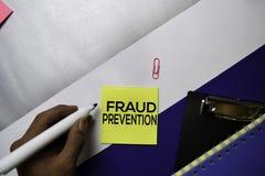Texto da prevenção de fraude em notas pegajosas com conceito da mesa de escritório da cor imagens de stock