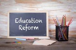 Texto da reforma da educação em um quadro-negro Tabela de madeira velha com textura fotografia de stock