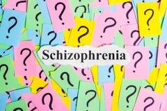 Texto da síndrome da esquizofrenia em notas pegajosas coloridas na perspectiva dos pontos de interrogação Imagem de Stock