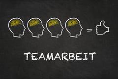Texto de 'Teamarbeit ', cabezas con el cerebro y pulgar en un fondo de la pizarra Traducción: 'Trabajo del equipo ' ilustración del vector