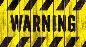 Texto de advertência da palavra do sinal do perigo como o estêncil com as listras amarelas e pretas pintadas no fundo largo do pa imagens de stock royalty free