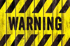 Texto DE ADVERTÊNCIA da palavra do sinal do perigo como o estêncil com as listras amarelas e pretas pintadas no fundo largo da te fotos de stock royalty free
