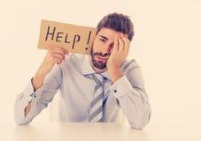 Texto de ayuda joven de Holding Cardboard With del hombre de negocios en el lugar de trabajo en la tensi?n y presi?n en el trabaj fotos de archivo libres de regalías