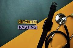 Texto de ayuno intermitente en la tabla de color de la visión superior y la atención sanitaria/el concepto médico fotos de archivo