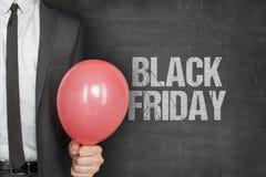 Texto de Holding Balloon With Black Friday do homem de negócios no quadro Fotografia de Stock