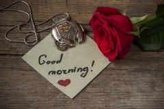 Texto de la buena mañana en un papel, una flor de la rosa del rojo y un EL de la decoración Fotografía de archivo libre de regalías