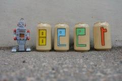 Texto de la cerveza pintado sobre las latas de cerveza con un robot del juguete de la lata Foto de archivo