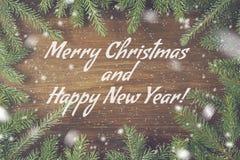 Texto de la enhorabuena de la Navidad en fondo de madera con el pino o las ramas y la nieve verdes del abeto Foto de archivo libre de regalías