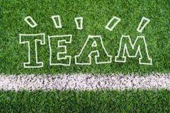 Texto de la escritura de la mano del EQUIPO en hierba del campo de fútbol ilustración del vector