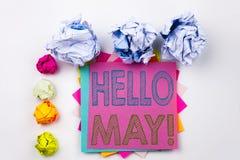 Texto de la escritura que muestra el hola mayo Primavera escrita en nota pegajosa en oficina con las bolas del papel del tornillo Fotografía de archivo