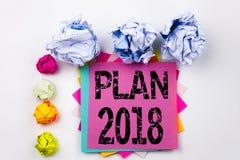 Texto de la escritura que muestra el plan 2018 escrito en nota pegajosa en oficina con las bolas del papel del tornillo Concepto  Fotos de archivo
