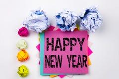 Texto de la escritura que muestra la Feliz Año Nuevo escrita en nota pegajosa en oficina con las bolas del papel del tornillo Con Imagen de archivo