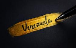Texto de la escritura de Venezuela en movimiento de oro de la brocha fotos de archivo