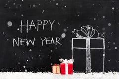 Texto de la FELIZ AÑO NUEVO con las cajas de regalo y nieve en la pizarra Imagen de archivo libre de regalías