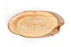 Texto de la Feliz Año Nuevo en el pedazo de madera Imagenes de archivo